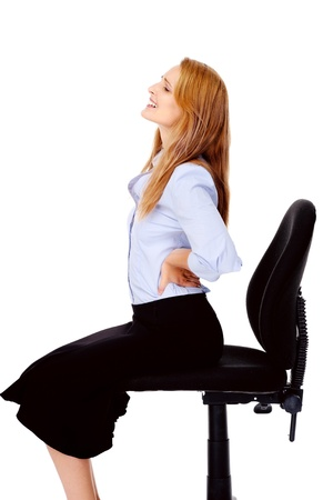 Young businesswoman suffers from back pain caused by her office chair