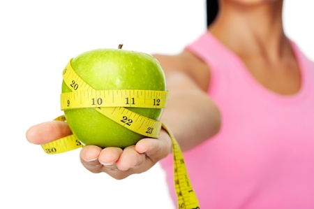 Foto de Healthy happy hispanic woman with apple and tape measure for diet and weight loss concept - Imagen libre de derechos