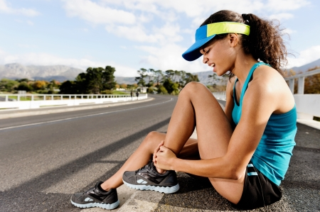 Runner with ankle injusry has sprained and strained ankle, painful expression. typical road running problem associated with shoe choice