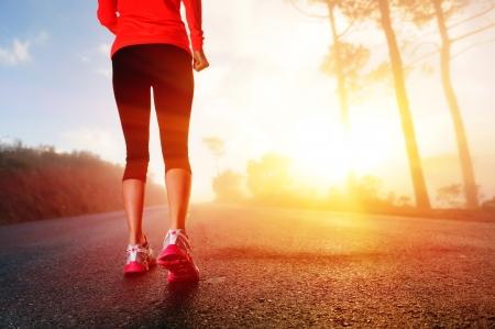 Athlete runner feet running on road closeup on shoe  woman fitness sunrise jog workout wellness concept