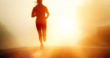 Runner athlete feet running on road  woman fitness silhouette sunrise jog workout wellness concept