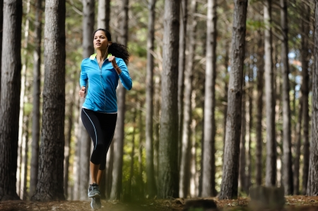 Woman running in wooded forest area, training and exercising for trail run marathon endurance  Fitness healthy lifestyle concept