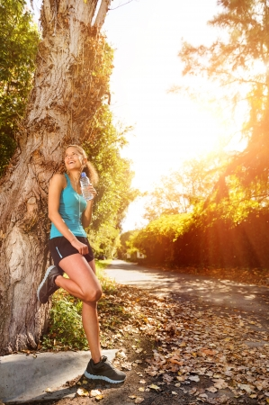 Photo pour healthy happy fitness woman resting in suburb with water bottle after workout exercise session. vitality lifestyle runner. - image libre de droit