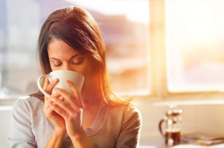 Photo pour Woman drinking coffee at home with sunrise streaming in through window and creating flare into the lens.  - image libre de droit