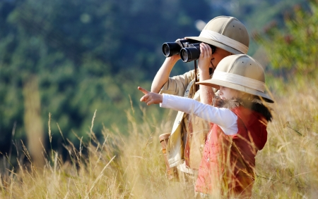 Foto de Children brother and sister playing outdoors pretending to be on safari and having fun together with binoculars and hats - Imagen libre de derechos