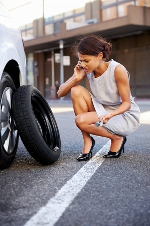 Photo for Woman calling for assistance with flat tire on car in the city - Royalty Free Image