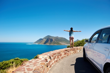 Foto de carefree tourist stands on chapmans peak drive with arms outstretched in freedom girl pose with rental car - Imagen libre de derechos