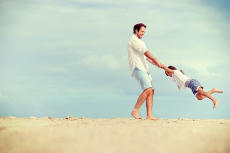 Foto de Healthy father and daughter playing together at the beach carefree happy fun smiling lifestyle - Imagen libre de derechos