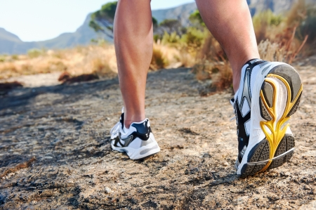 trail running athlete feet on rock excercising fitness and healthy lifestyle