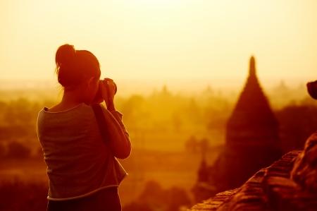female traveller photographing temples at Bagan Myanmar Asia at sunrise