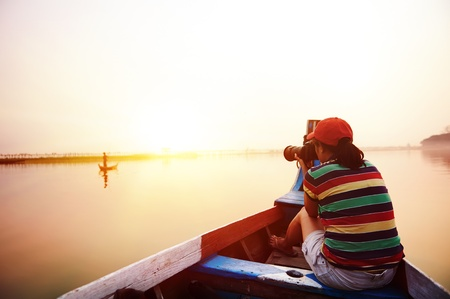 Female backpacker on vacation taking photo of local fisherman on boat in asia sunset