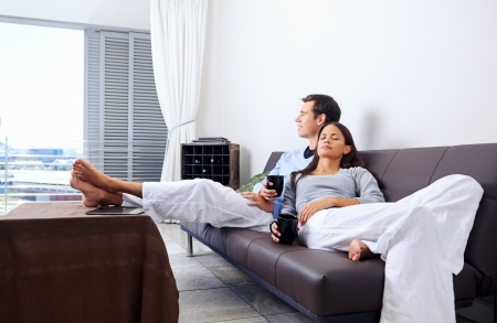 Photo pour Couple relax at home with cup of coffee and sofa couch. happy healthy relationship - image libre de droit