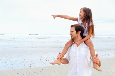 daughter on dad shoulders pointing while at the beach