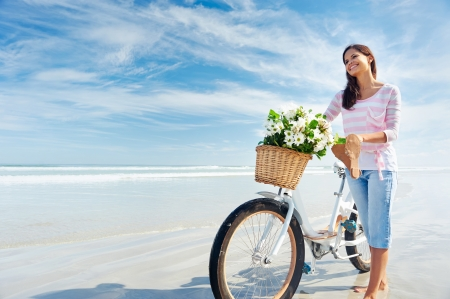 woman with bicycle and flowers in basket smiling carefree and happy