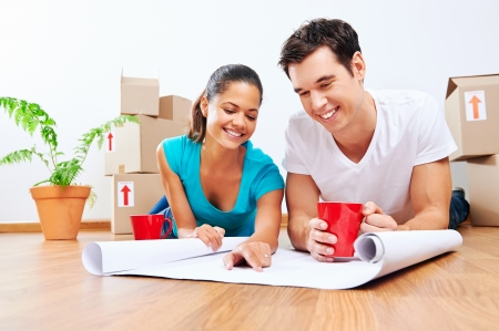 Photo for couple lying on floor looking at plans of new house together while drinking coffee and laughing - Royalty Free Image