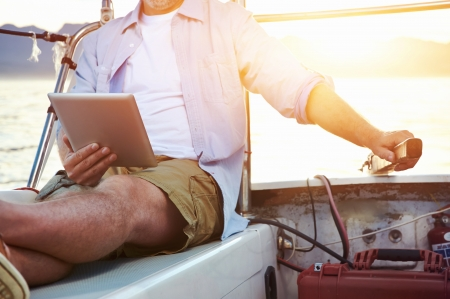Foto de sailing man reading tablet computer on boat with modern technology and carefree retired senior successful lifestyle - Imagen libre de derechos