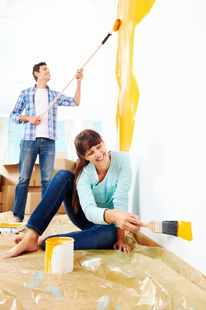 Photo for renovation diy paint couple in new home painting wall - Royalty Free Image