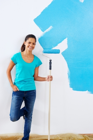 portrait of woman posing with paint roller in new apartment renovation