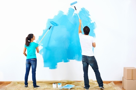 Photo pour couple painting new home together with blue color happy and carefree relationship - image libre de droit
