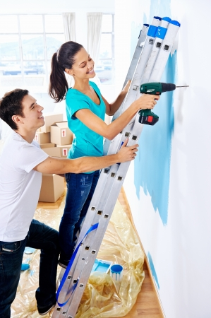 Photo pour couple drilling in wall doing diy at new home after moving in together - image libre de droit