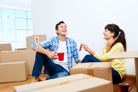 couple celelbrating new home handing keys and moving boxes