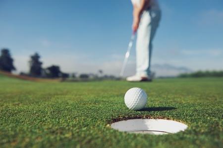 Photo pour Golf man putting on green for birdie - image libre de droit