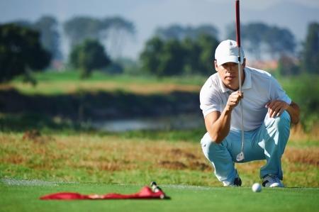 Photo pour Golfer aiming lining up putt on green - image libre de droit