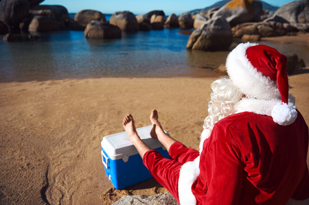 Father Christmas relaxing on the beach resting his bare feet on his cooler while looking at the view