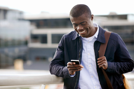Photo pour happy young black african man with cell phone having conversation on mobile - image libre de droit