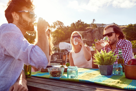 Photo pour Group of friends sitting hanging out with drinks on the rooftop - image libre de droit