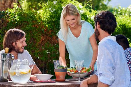 Photo pour young woman serving salad to friends gathering at outdoor garden party - image libre de droit