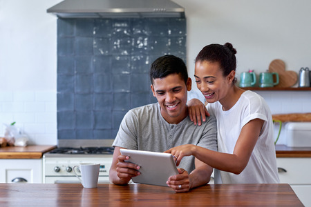 Foto de couple bonding and enjoying morning coffee with tablet computer in kitchen at home - Imagen libre de derechos