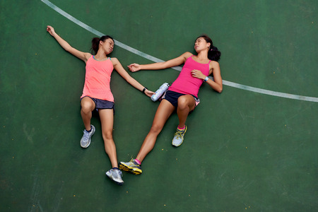 exhausted sporty women runners laying on basketball court after fitness running workout outdoors