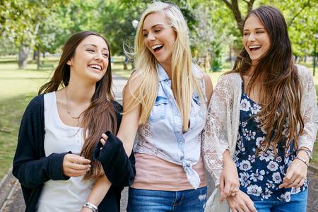 happy fun teen girl friends walking in park laughing on weekend