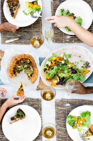 Overhead view of group of friends, hands serving up fresh organic platters of food laid out on a table, a casual outdoor dining party setting