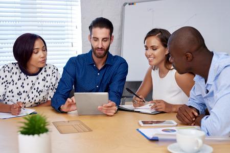 Foto de diverse multiracial colleagues discussing tech startup business ideas on tablet computer device - Imagen libre de derechos