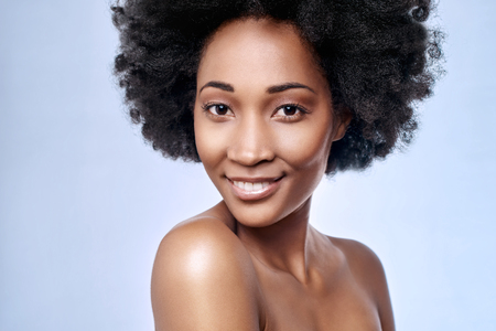 Portrait of beautiful black african model smiling in studio with smooth complexion flawless skin