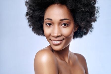 Foto de Portrait of beautiful black african model smiling in studio with smooth complexion flawless skin - Imagen libre de derechos