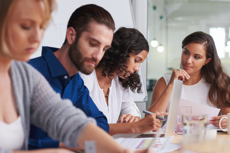 coworkers meeting in boardroom to discuss ideas for company productivity at work