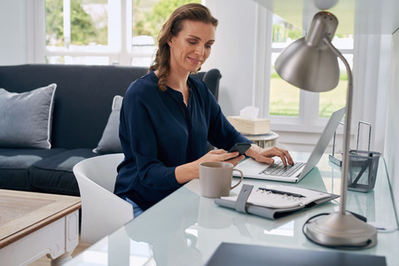 Photo for Mature successful business woman looking at mobile cell phone while at home in office work space - Royalty Free Image