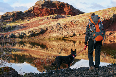 Photo pour Woman with backpack and pet dog looking over the scenic lake and enjoying the view after a hard hike - image libre de droit
