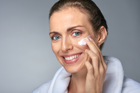 Foto de portrait of beautiful radiant mature woman applying some cream to her face, skin care cosmetics wellness concept - Imagen libre de derechos