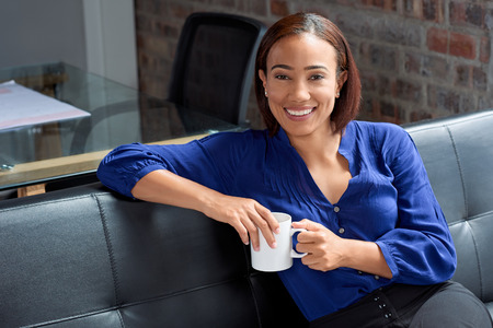 Asian business woman smiling in office with a coffee, confident successful person portrait
