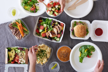 Photo pour Convenient takeaway takeout food for party, overhead spread of assorted food with hands serving up - image libre de droit
