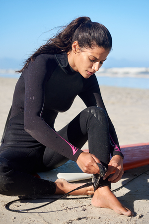 Photo pour Surfer in wetsuit sitting on surfboard tying leash to ankle before hitting the waves - image libre de droit