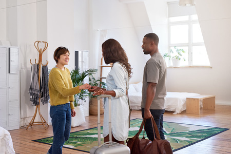 Asian woman welcomes black couple into her house home accommodation for their holiday vacation trip