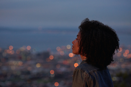 Beautiful thoughtful woman with afro looking out to city below her, lights coming on at twilight