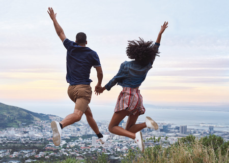 Couple holding hands and jumping in the air with raised arms excited to be on holiday viewpoint overlooking foreign city