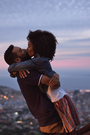 Photo pour Young carefree romantic love affair, loving couple kissing at sunset with city lights - image libre de droit