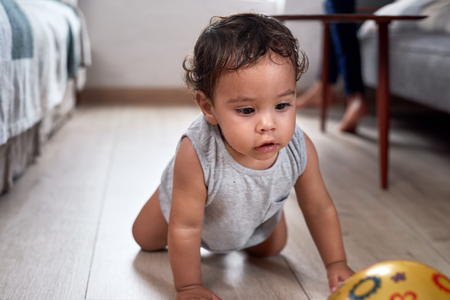Foto de Cute mixed race baby boy crawling after a ball, learning how to walk - Imagen libre de derechos
